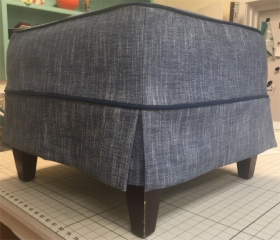 Footstool covered with grey textured fabric and piping accent