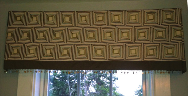 Geometric-patterned cornice with hanging beads, mounted on window