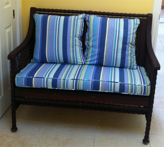 Blue, green and white striped cushions and pillows on wicker love seat