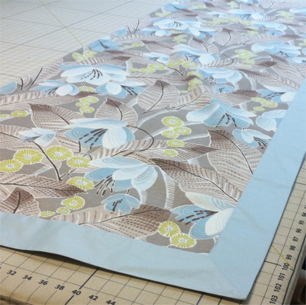 Fabric with flowers and leaves and blue border laid out on cutting table