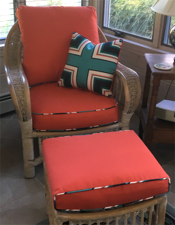 Wicker lounge chair on sun porch with burnt orange cushions and piping, geometric pattern throw pillow