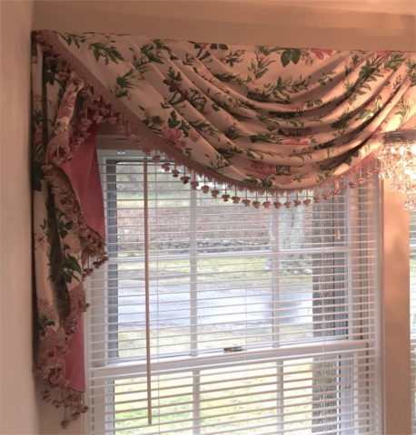 Flower patterned fabric drape with fringe over window