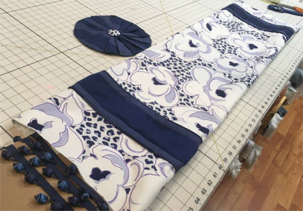 Custom drapes in progress of blue flowered fabric with dark blue accent material, on worktable