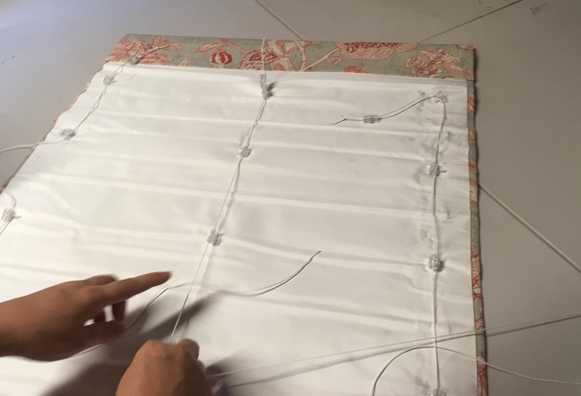 Two hands on sewing table and back of in-process roman shades
