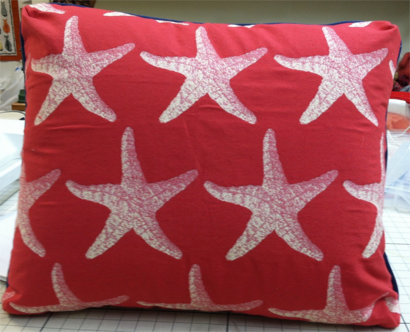 Square throw pillow in red fabric with stenciled textured sea stars