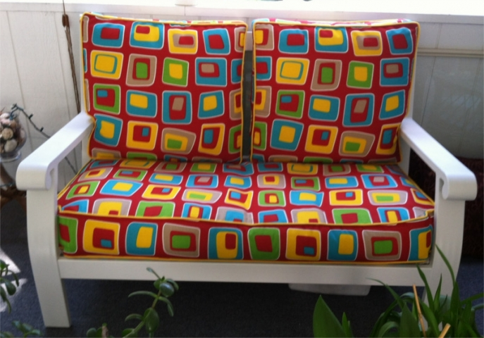 Colorful geometric patterned cushions on porch furniture love seat