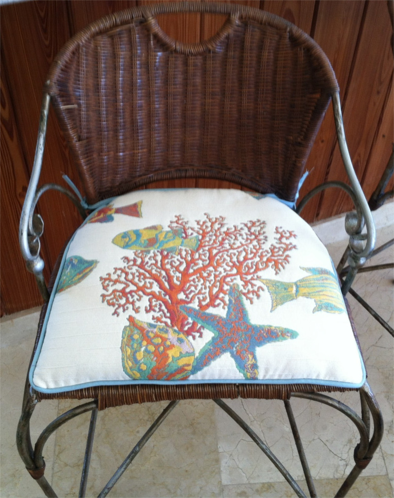 Custom hand-sewn perfectly-fitted cushion of underwater sea scene fabric on metal and wicker chair