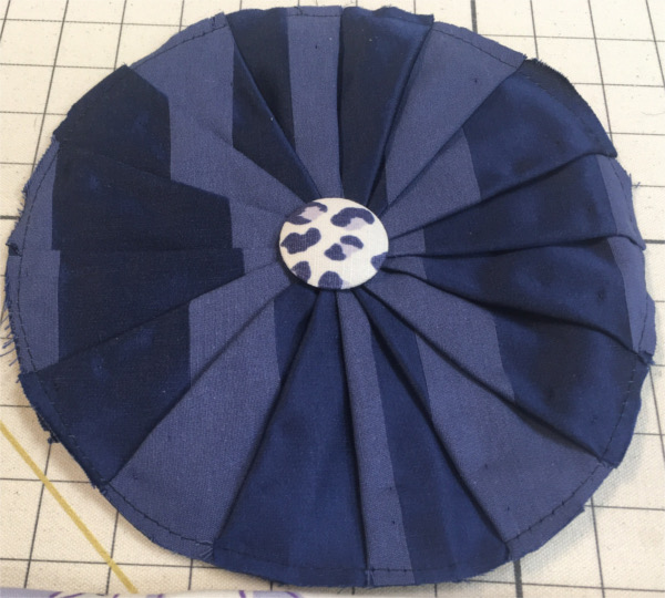Cushion in two-toned blue pleated fabric with button in center
