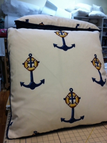 Anchor pattern on throw pillow with navy blue corded piping