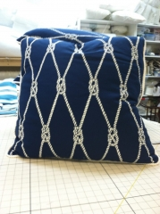 Patterned throw pillow with solid white cord piping