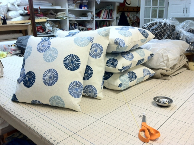 Five matching throw pillows on work table