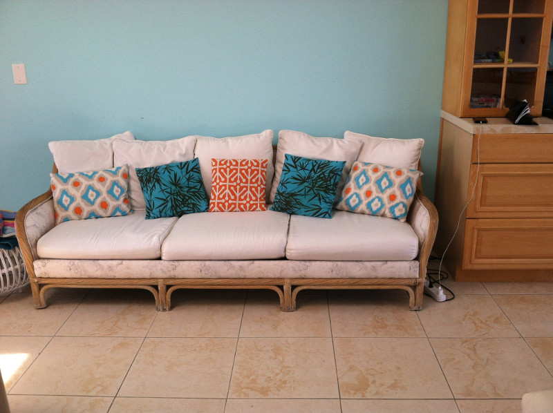 Upholstered couch, couch cushions of muted solid color with throw pillows of contrasting bright colors, all hand-sewn