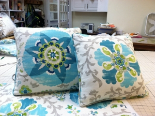 Two throw pillows with piped edging with centered design from same fabric but different pattern to each