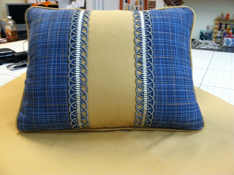 Throw pillow with decorative braid and piped edging