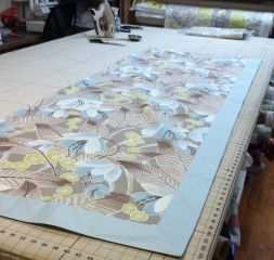 On the work table, fitting fabrics together for the perfect drapes