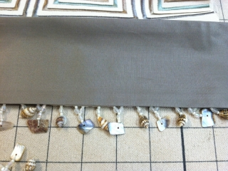 Closeup of hanging shell fringe on valance curtain