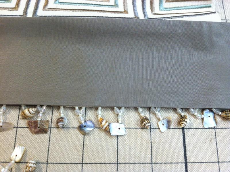 Closeup of hanging shell fringe on valance curtain