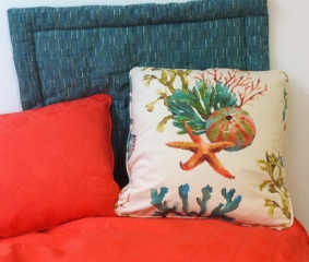 Three throw pillows of complementary colors; two with piping and one with inset stitching
