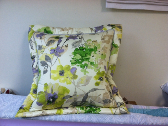 Throw pillow with deep stitched edging and inset piping of a flower pattern