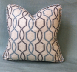 Throw pillow with rolled piped edging and geometric pattern