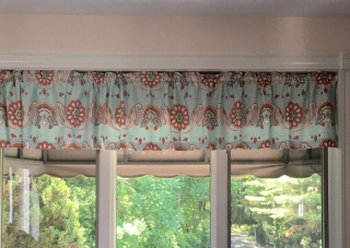 Valance drape with vertical pleats hanging on window