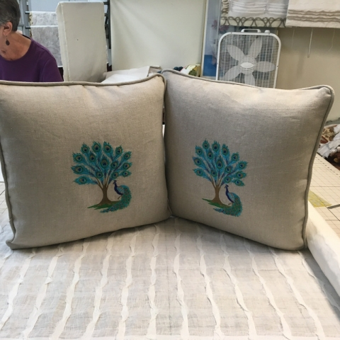 Two matching throw pillows with centered peacock pattern and piped edging