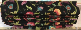 Closeup of gathered fabric of roman shade with black background and colorful flowers