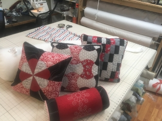 Three quilt-patterned throw pillows of mixed fabrics and matching small bolster