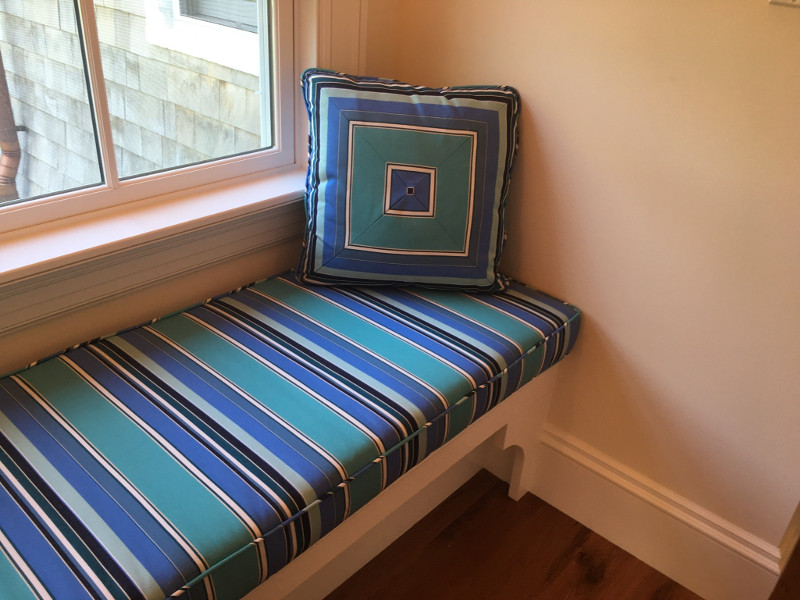 Striped window seat cushion with piped edging and matched square pillow of four perfectly-aligned panels