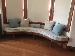 S-curved window seat cushion and matching patterned throw pillows