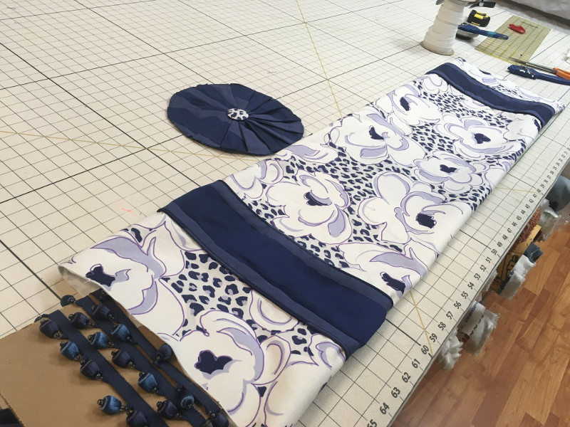 Blue flowered fabric with solid navy blue bands and bead fringing on work table; to be roman shades