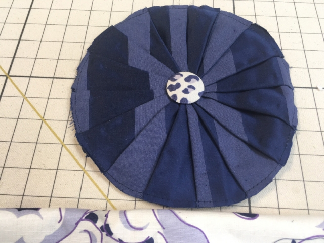 Round pleated fabric with button center on work board, work in process