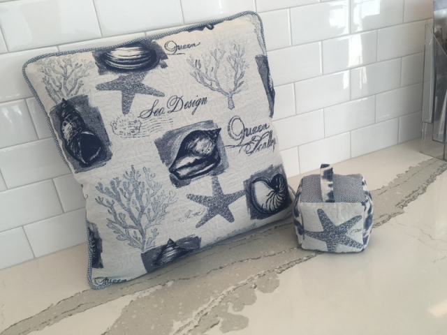 Patterned throw pillow with piped edging and matching fabric doorstop
