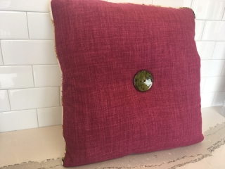 Square throw pillow with patterned piped edging and centered button