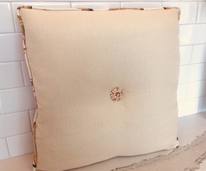 Square throw pillow with piped edging and matching fabric button center