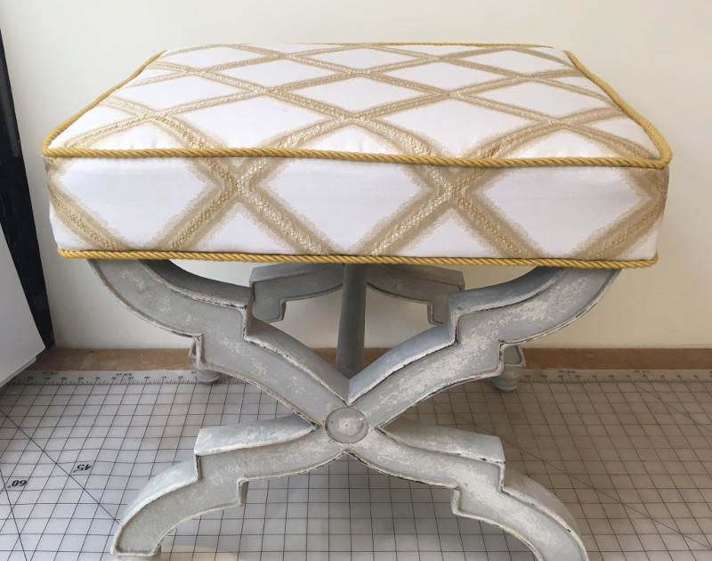 Rectangular seat cushion with gold piping and fabric pieces perfectly aligned