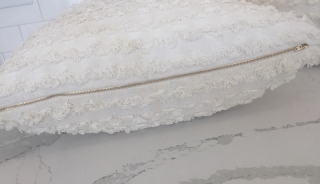 Detail of hand-sewn zippered white throw cushion cover