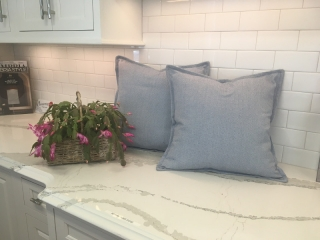 Square slate gray throw pillows with piping around edges