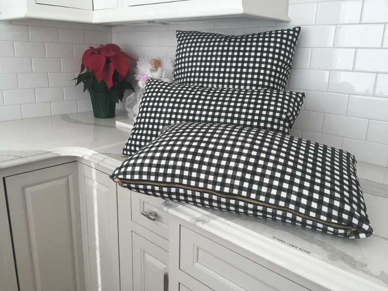 Three black and white checked throw pillows with zippers for easy case removal