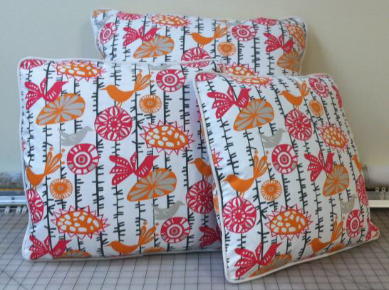 Three colorful bird and flower fabric pillows with white piping
