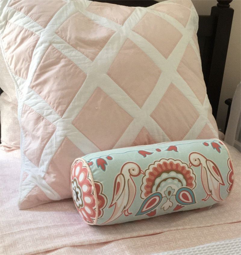 Ornately hand-sewn diamond pattern square pillow with small bolster