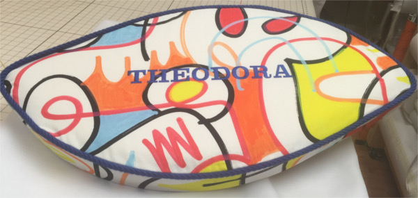 Wavy custom-shaped pillow with bold geometric print pattern and name of Theodora