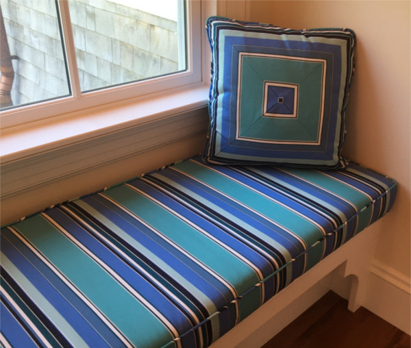 Window seat with blue, green and black striped cushion and throw pillow