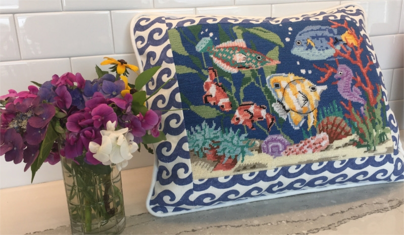 Rectangular pillow, embroidered underwater sea animal scene, wave fabric border and white piping, next to bouquet of local flowers